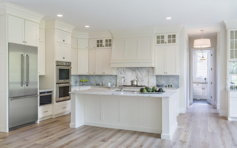 Kitchen with cream colored cabinets and marble backsplash