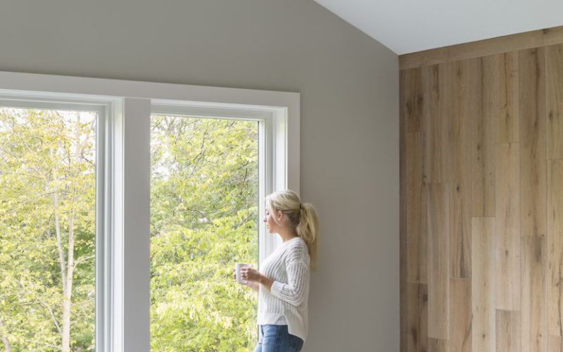 Woman looks out window in new house