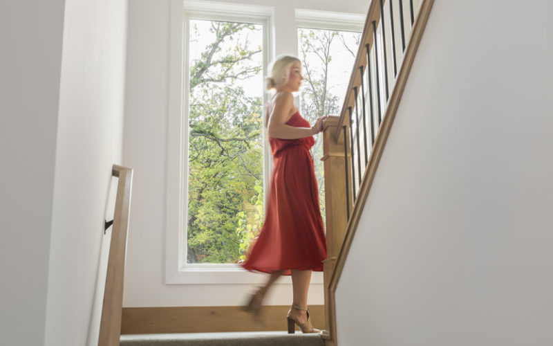 Woman in red dress walking up stairs